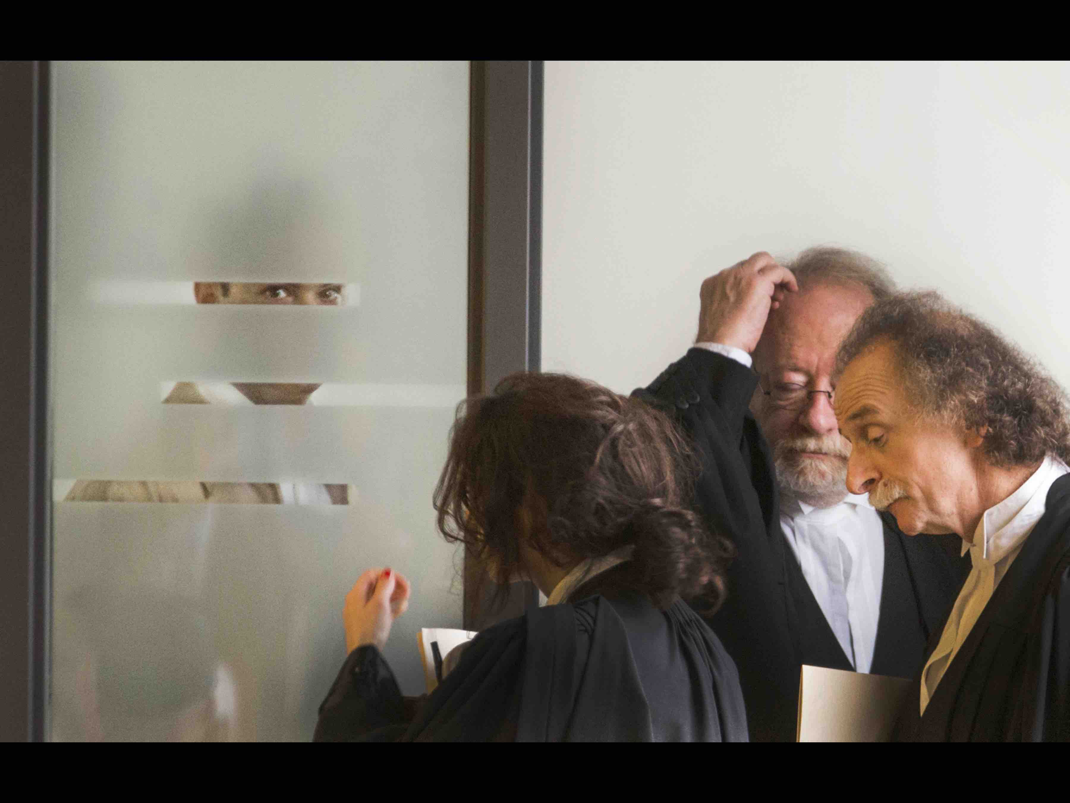 """Titre: """"Dans les yeux de Guy Turcotte"""" Catégorie: Nouvelles Deuxième procès de Guy Turcotte. Photo prise au palais de justice de Saint-Jérome, Quebec. Sur la photo: (Gauche a droite) Guy Turcotte que l'on voit ici regarder à travers une porte vitrée, était présent dans le box des accusés lors du témoignage de son ex-femme, Isabelle Gaston. Il était accompagné de nombreux avocats. 28/09/2015 le 28 Septembre, 2015 Photo pour La Presse Plus. -30"""