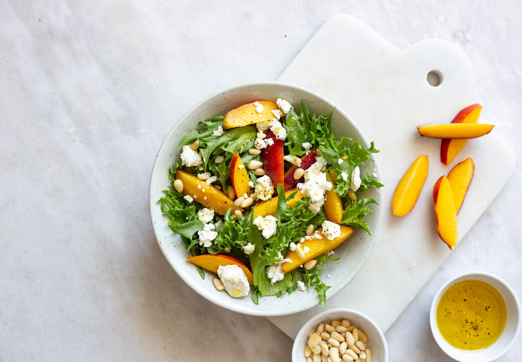 Autumn salad of iceberg lettuce, spinach, peach and goat cheese in a white rustic plate on marble background with copy space