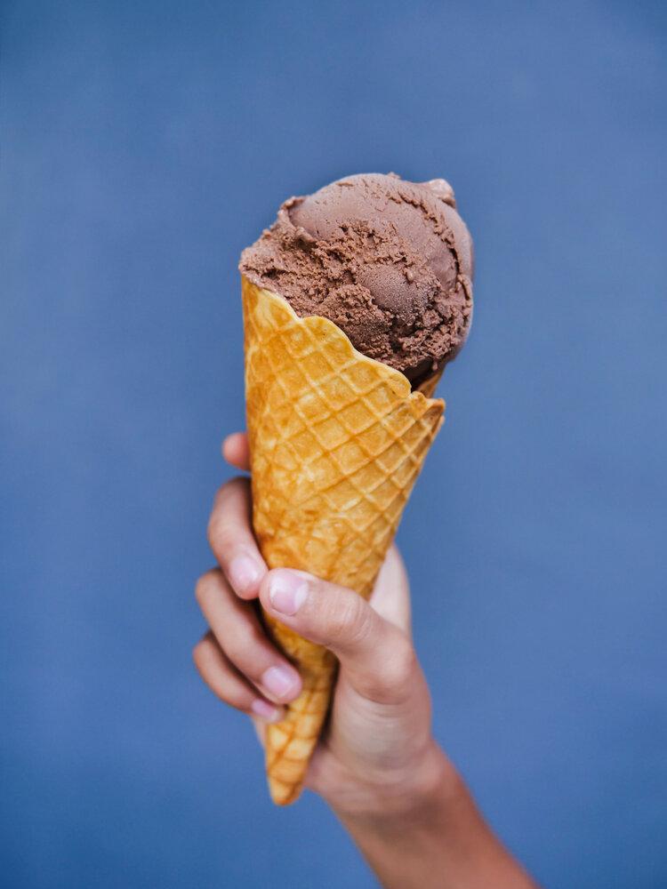 Kid hand holding chocolate ice cream cone with blue wall.